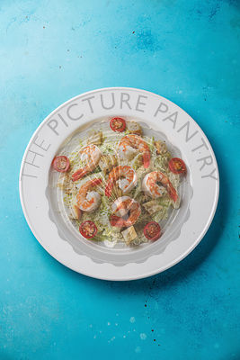 Caesar salad with shrimps and croutons on blue background copy space