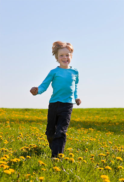 Boy running in field of flowers