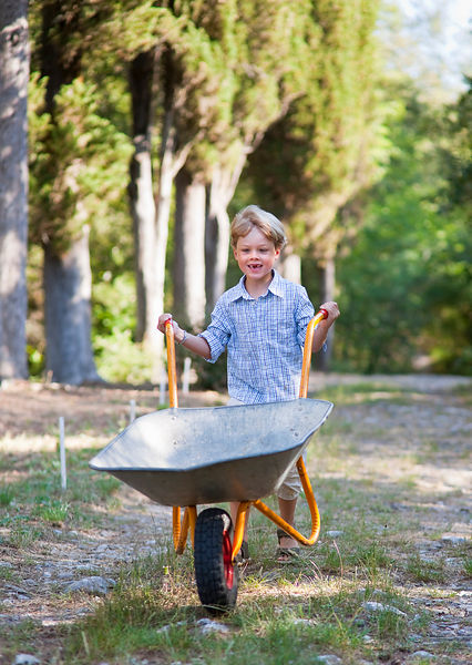 Boy pushing wheelbarrow outdoors