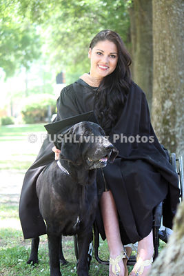 Young woman in a wheelchair at her graduation with her service dog