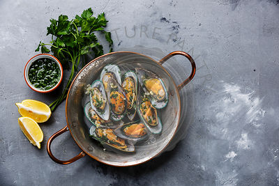 Shellfish Mussels Clams in copper cooking pan with parsley and lemon on concrete background copy space