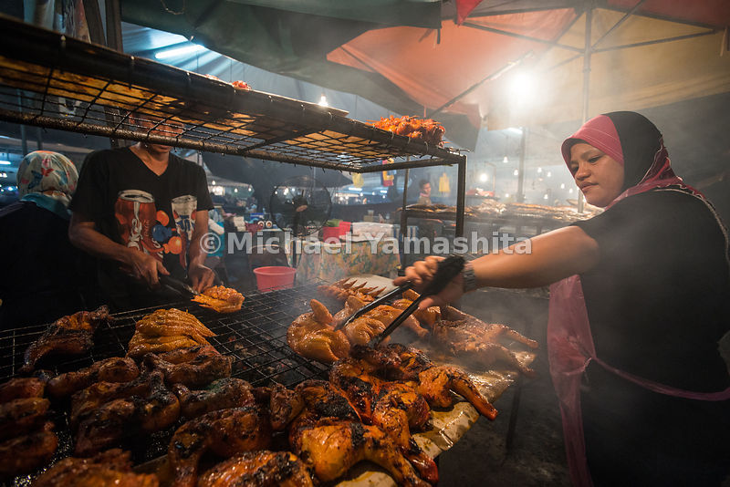Chef cooks chicken on a large grill. Tasek Merimbun Lake