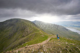 Two hikers walking along Swirl Band towards the summit of the Old Man of Coniston in the English Lake District.