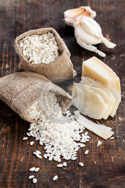 Raw white rice in burlap bag with ingredients for risotto