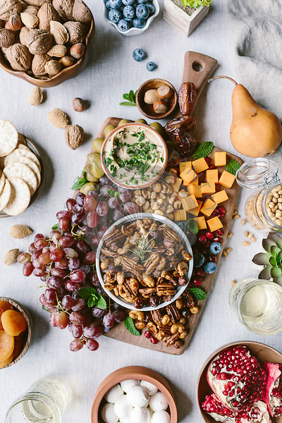 A bowl of spicy candied pecans are photographed as a part of a cheese and fruit board.