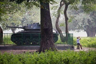 A man does yoga near a tank on the Maidan, Kolkata, India. The tank is a reminder of the horrrors of war.
