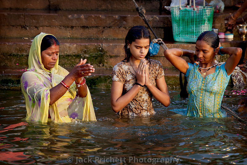 Hindu women worship and make offerings in the Ganges River at Varanasi (Benares).
