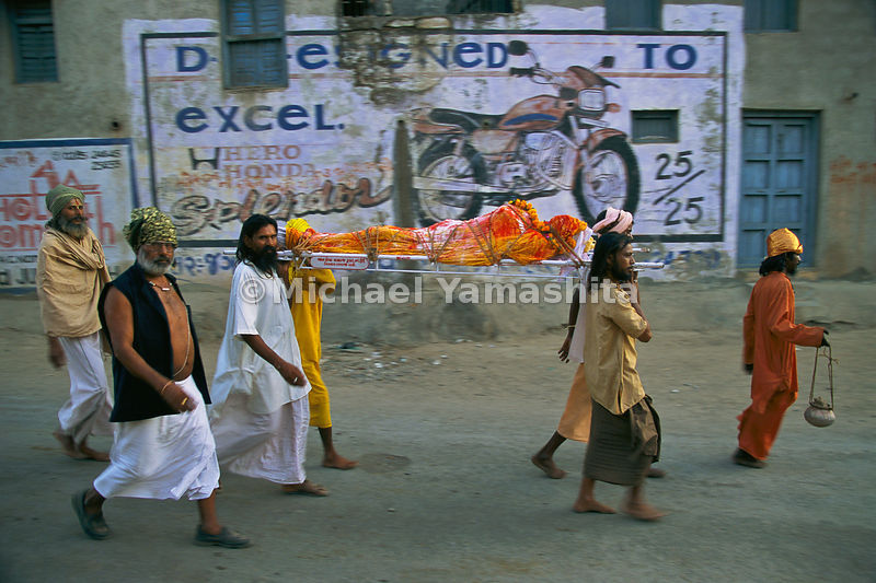 A dead holy man is carried to his funeral pyre in Junagadh.
