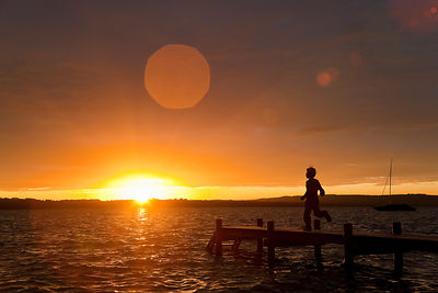 Boy running on wooden dock at sunset