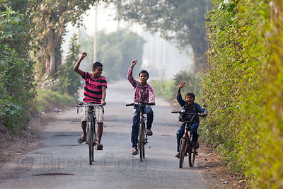 Children ride the bikes on a rural road near the Dhapa Dumping Ground, the primary landfill for Kolkata, India.