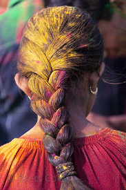 Yellow gulal powder on a girl's ponytail at the the Ganesh Chaturthi festival, Mumbai, India
