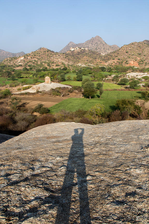 Wheat fields, large rocks and old temples, Rajgarh village, Rajasthan, India. In the distant at center is old Rajgarh fort.