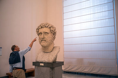 A man points to a bust in the National Archaeological Museum in Naples