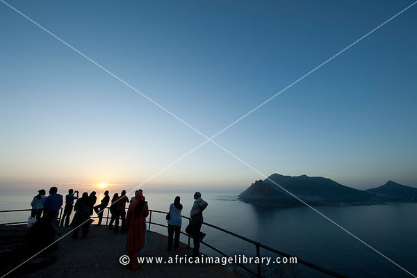 Tourists at dusk at a viewpoint on Chapman's Peak drive, Cape Town, South Africa