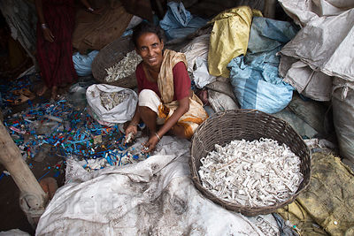 A woman recycles medical waste plastic with no health safeguards, Dhapa, Kolkata, India. Dhapa is a large industrial zone tha...