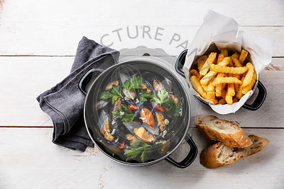 Shellfish Mussels Clams in black cooking dish pan and French Fries on white wooden background