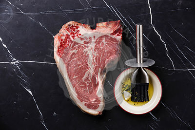 Raw fresh meat Dry Aged Steak T-bone and seasoning on dark marble background