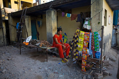 India - New Delhi - A girl in a red dress sits on the main road in Chirag Delhi