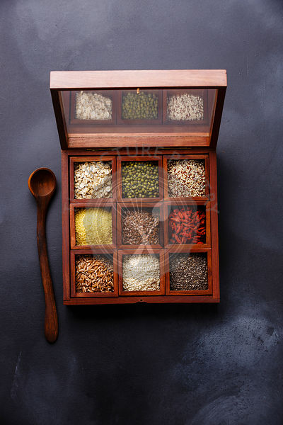 Superfoods and cereals selection in wooden box: oat, mung, quinoa, bulgur, flax seed, goji berry, polba, sesame and chia on d...