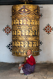 Large prayer wheel and an old man at the Chimi Lhakhang Monastery or temple, in Punakha District, Bhutan..Built in 1499, the ...