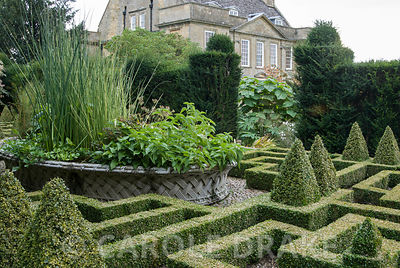 Basket pond at the centre of the Knot Garden came from the 1851 Great Exhibition, with form of Bourton House glimpsed through...