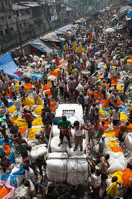 A trucks slowly passes through the crowded main avenue of the Howrah Flower Market in Kolkata, India, reputed to be the large...