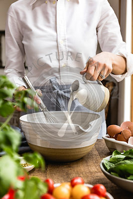 A woman mixing ingredients in a mixing bowl