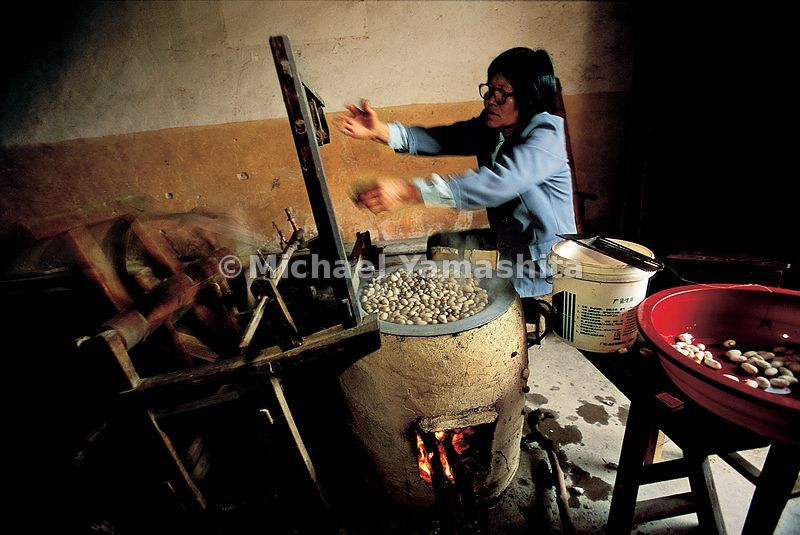 A woman boils silk cocoons to separate the threads.