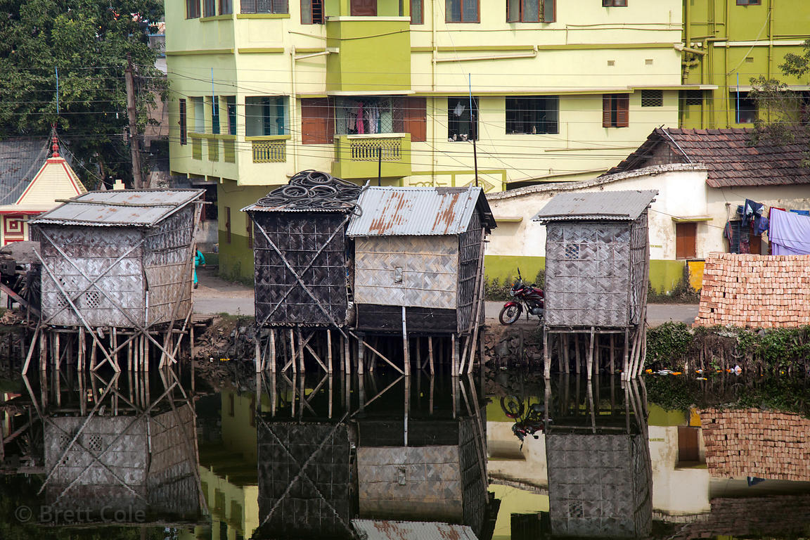 Huts and buildings reflecting in a pond in 24 South Parganas, south of Kolkata, India.