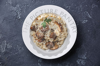 Risotto with porcini mushrooms serving size on dark stone background