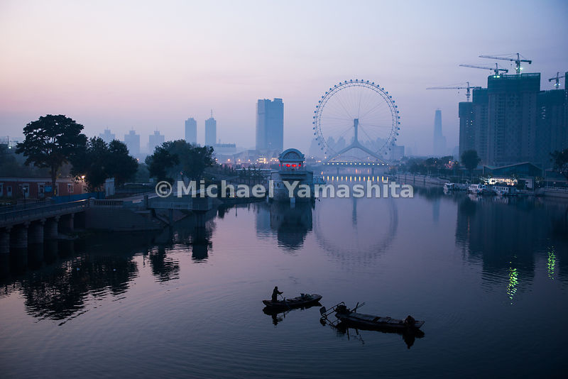 Fishermen work the Hai River in the shadow of the Ferris wheel in Tianjin. The Hai, which flows through Tianjin, fills a stre...