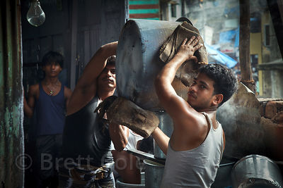 Men in the Dharavi slum in Mumbai, India make large quanitities of milk and bread pudding in a sweltering workshop,