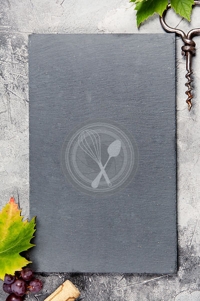 Top view of a blank chalk board for a wine list or menu with an old cork screw and grape leaf on gray concrete background wit...