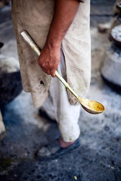 India - Srinagar - Wazas, A Waza, a traditional Kashmiri cooks, holds a spoon whilst preparing a Wazwan a Kashmiri feast