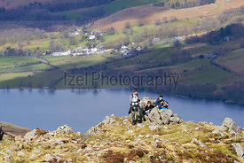 Three hikers resting near the summit of Hay Stacks with views of Buttermere in the background in the English Lake District.