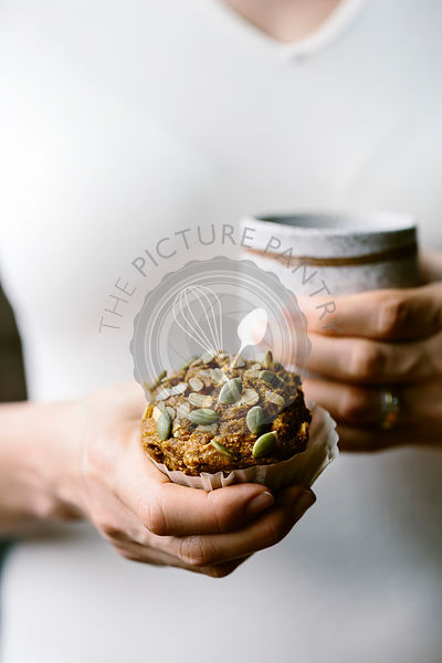 A woman is holding a freshly baked Maple Sweetened Pumpkin Oat Muffin in her hand while holding a cup of coffee in her other ...