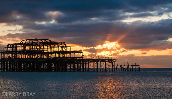 West Pier against sunset a rays of sun in Brighton, East Sussex, UK