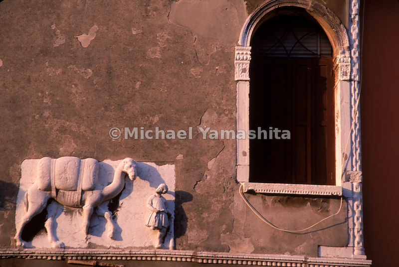 A camel and merchant are immortalized on the facade of a palace in Cannaregio.