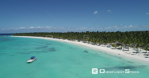 Caribbean beach with palm trees. Flight forward over the sea and boats . Saona Island, Dominican Republic