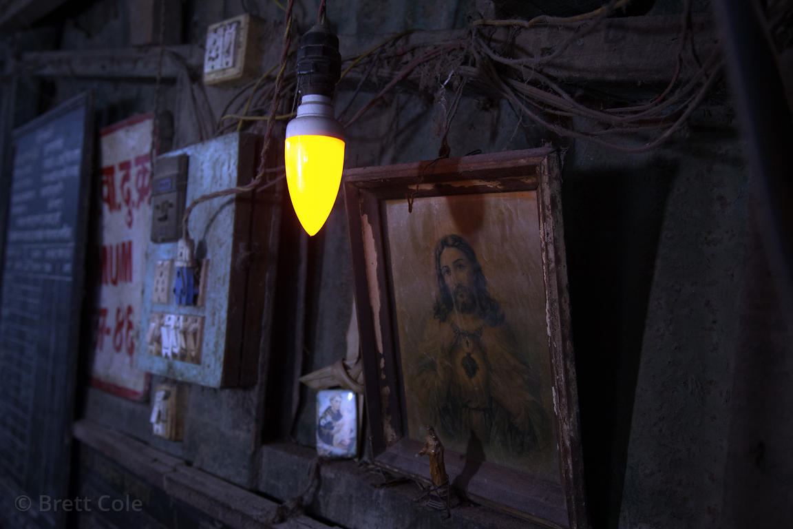 A lightbulb in a market stall illuminates a small painting of Jesus, Sion, Mumbai, India.