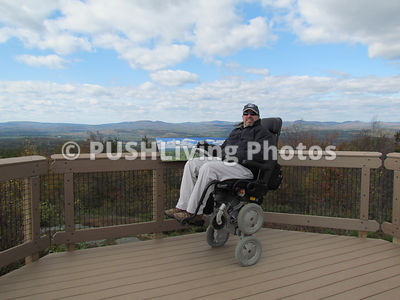 Man in a power wheelchair on an observation deck in a national park