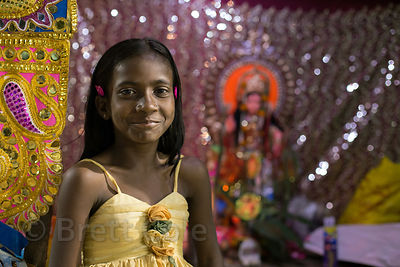 A girl stands next to her family's small Durga Puja pandal, Babughat, Kolkata, India