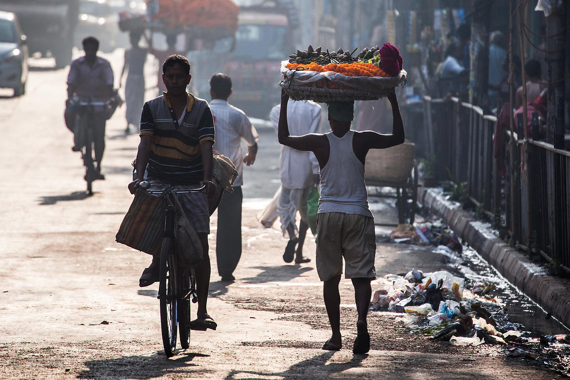 A man carries marigold garlands in a basket on his head, early morning near Howrah Bridge, Kolkata, India.