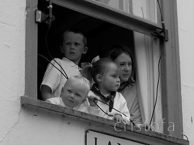 a family in Padstow watch the Obby Oss parade