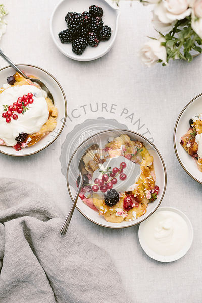 A goat cheese & berry bread pudding is photographed from the top view after it was placed in bowls and topped off with creme fraiche and red currants.