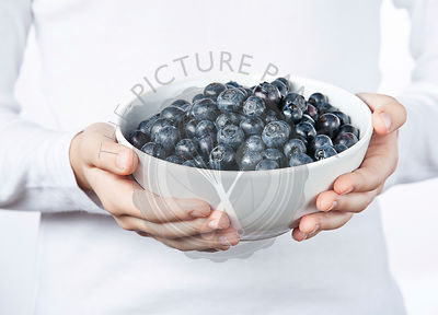 Children's hands holding blueberries in white bowl