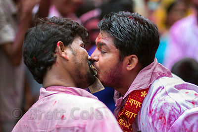 Men covered in gulal powder exchange a rupee note from mouth to mouth during the Ganesh Chaturthi festival in Delhi, India