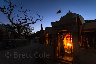 "Pujari lights a fire at the 7th century Ajaypal temple site (Shiva temple), near Pushkar, Rajasthan, India. Taken on the ""Bla..."