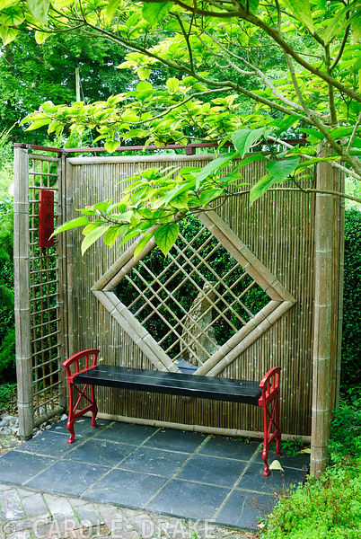 Bamboo screens frame a bench in the Scholar's Garden. Beggars Knoll, Newtown, Westbury, Wiltshire, UK