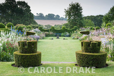 Topiary castles complete with flags overlook the herbaceous borders. Felley Priory, Underwood, Notts, UK